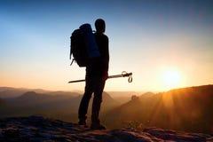 一个高人的锋利的剪影在山的上面的与太阳的在框架 在山的旅游指南 图库摄影