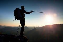 一个高人的锋利的剪影在山的上面的与太阳的在框架 在山的旅游指南 免版税库存照片