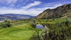 一个高尔夫球场在Osoyoos有Osoyoos湖的不列颠哥伦比亚省加拿大附近的欧肯纳根谷在背景中 库存图片