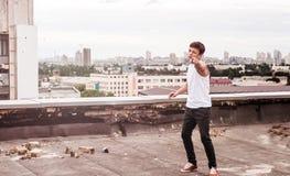 一个高楼的屋顶的少年 免版税库存照片