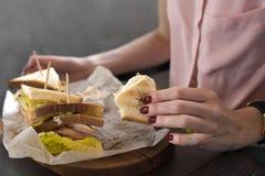 一个鲜美健康开胃汉堡的三明治在一个少妇的手上有膳食在餐馆 免版税图库摄影