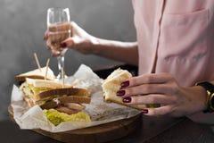 一个鲜美健康开胃汉堡的三明治在一个少妇的手上有膳食在餐馆 免版税库存图片