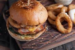 一个鲜美汉堡的特写镜头用开胃菜例如油煎的洋葱圈用白色蒜酱油 水多的汉堡用烟肉和乳酪 免版税图库摄影