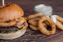 一个鲜美汉堡的特写镜头用开胃菜例如油煎的洋葱圈用白色蒜酱油 水多的汉堡用烟肉和乳酪 免版税库存图片
