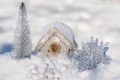 一个鸟舍、一个房子鸟的在雪与圣诞树和银色发光的雪花装饰 快活的圣诞节 库存图片