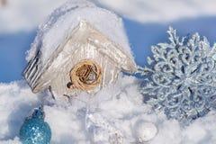 一个鸟舍、一个房子鸟的在雪圣诞树玩具和银色发光的雪花装饰 圣诞节愉快快活新 免版税图库摄影
