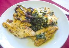 一个鸡内圆角用菠菜沙拉和油煎的夏南瓜 库存照片