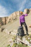 一个黄色帽子和一个对的微笑的女孩旅客太阳镜站立在史诗岩石的脚与下的背包的和 免版税库存照片
