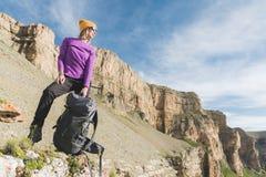 一个黄色帽子和一个对的微笑的女孩旅客太阳镜站立在史诗岩石的脚与下的背包的和 库存图片