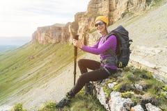 一个黄色帽子的微笑的女孩旅客和ssitting在史诗岩石的脚的一个对太阳镜与下的背包的 库存图片