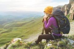 一个黄色帽子的微笑的女孩旅客和ssitting在史诗岩石的脚的一个对太阳镜与下的背包的 图库摄影