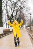 一个黄色斗篷的愉快的男孩显示类推力他的赞许 库存图片