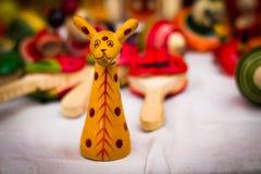 一个黄色木长颈鹿形象反对被弄脏的背景的葡萄酒玩具 库存照片