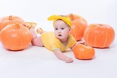 一个黄色身体的俏丽的女婴与在她的头的一把黄色弓 库存照片
