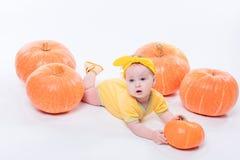 一个黄色身体的俏丽的女婴与在她的头的一把黄色弓 免版税库存图片