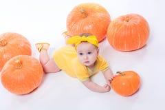 一个黄色身体的俏丽的女婴与在她的头的一把黄色弓 免版税图库摄影