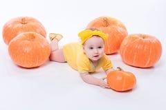 一个黄色身体的俏丽的女婴与在她的头的一把黄色弓 免版税库存照片