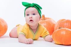 一个黄色身体的美丽的女婴与在她的头的绿色弓 库存照片
