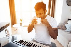 一个黑人在他的公寓客厅坐并且播放合成器 他组成音乐并且喝咖啡 免版税库存图片
