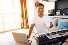 一个黑人在他的公寓客厅坐并且播放合成器 他组成音乐并且喝咖啡 免版税图库摄影