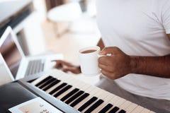 一个黑人在他的公寓客厅坐并且播放合成器 他组成音乐并且喝咖啡 库存照片