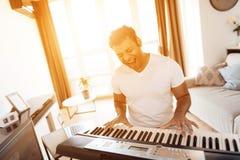一个黑人在他的公寓客厅坐并且播放合成器 他组成音乐 库存图片