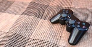 一个黑塑料无线比赛控制器的特写镜头照片在方格的织物覆盖系数背景的  比赛控制杆 让` s去pla 图库摄影
