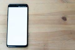 一个黑手机的图象的顶视图嘲笑有白色屏幕的在葡萄酒木桌背景 免版税库存照片