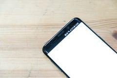 一个黑手机的图象的顶视图嘲笑有白色屏幕的在葡萄酒木桌背景 库存图片