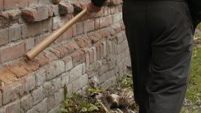 一个黑敞篷的一个街道小流氓在工地工作触击了有一个木棒的一个砖红色砖墙 影视素材