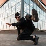 一个黑时兴的被编织的帽子的专业年轻人舞蹈家在运动鞋的牛仔裤在时髦的衬衣跳舞的太阳镜 库存照片