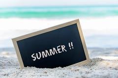 一个黑板的特写镜头与在海滩的沙子写的文本夏天 免版税库存照片