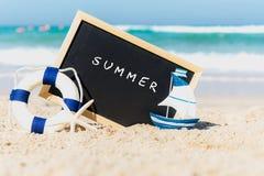 一个黑板的特写镜头与在海滩的沙子写的文本夏天 库存图片
