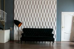 一个黑沙发和一盏黑落地灯反对白色装饰了墙壁在顶楼空间 免版税库存照片