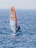 一个黑田径服的年轻运动员行使在风帆冲浪的在地中海在纳哈里亚,以色列 免版税图库摄影