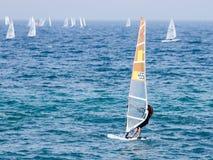 一个黑田径服的年轻运动员行使在风帆冲浪的在地中海在纳哈里亚,以色列 免版税库存照片