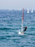 一个黑田径服的年轻运动员行使在风帆冲浪的在地中海在纳哈里亚,以色列 库存照片