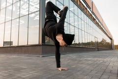 一个黑被编织的帽子的美国年轻人舞蹈家在一件时髦的衬衣的运动鞋在牛仔裤在玻璃大厦附近跳舞户外 图库摄影