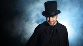 一个黑高顶丝质礼帽和斗篷的人 恶魔般的图象 魔术师魔术师 库存图片