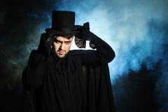 一个黑高顶丝质礼帽和斗篷的人 恶魔般的图象 魔术师魔术师 免版税库存图片