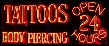 一个24个小时纹身花刺客厅霓虹灯广告 免版税库存图片