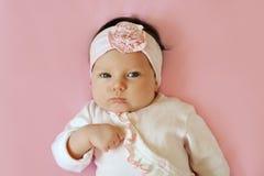 一个2个月逗人喜爱的女婴佩带的鞋带花头饰带和躺下的画象在桃红色毯子 免版税库存照片