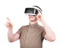 一个年轻人使用一个3D虚拟现实耳机,隔绝在白色背景 新和专业音响器材 免版税库存图片