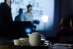 一个年轻人和一个少妇戏院的看一个白色屏幕坐一把椅子在黑暗 免版税图库摄影