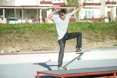 一个年轻人在一个指南的一个滑板滑在房子背景的一skatepark  免版税库存图片