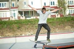 一个年轻人在一个指南的一个滑板滑在房子背景的一skatepark  库存图片