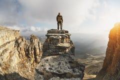 一个年轻人在峭壁围拢的岩石站立,在云彩上一个巨大地点,位于背景  免版税库存照片