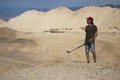 一个年轻人在拿着智能手机和行动照相机的沙漠站立 库存图片