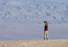 一个年轻人在有智能手机的沙漠拍一张照片 免版税图库摄影