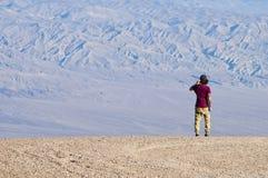 一个年轻人在有智能手机的沙漠拍一张照片 免版税库存图片